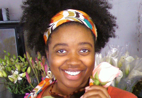 woman smiling at camera, holding flower
