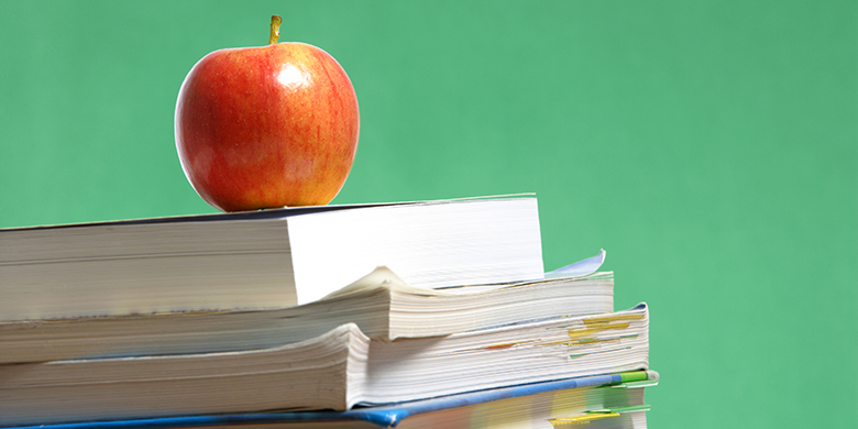 stack of college textbooks with an apple
