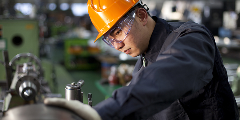 man in hard hat working with manufacturing tool