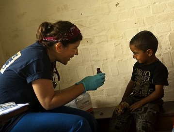 woman wearing medical gloves talking to young boy