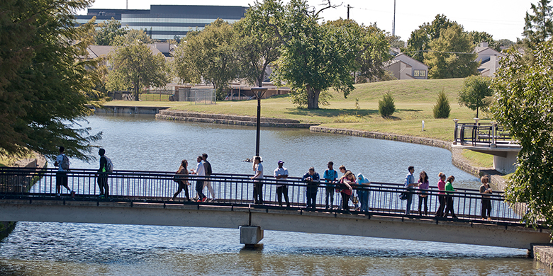 Students walking across a bridge on a college campus.