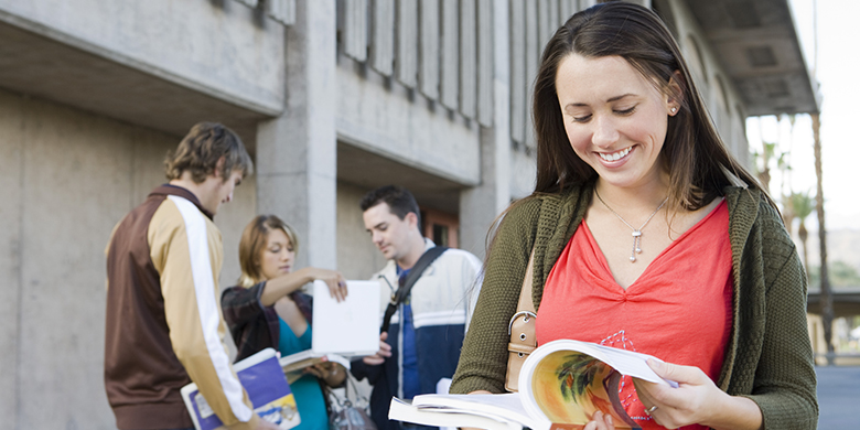 Female college student holding book, outdoors