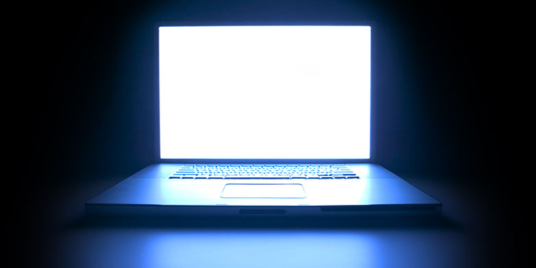 laptop computer as the screen glows in the darkness