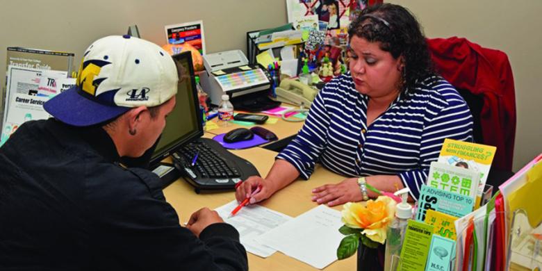Academic Advisor Nadia Rodriguez helps a student look over his transcript.