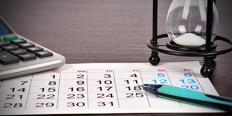 pen, hourglass and calendar laying on a desk