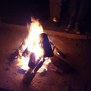 A campfire burns as student leaders stand nearby.