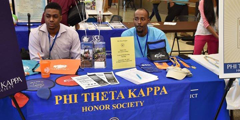 William Kaseu and a friend sit at the Phi Theta Kapp table at a DCCCD fair together.