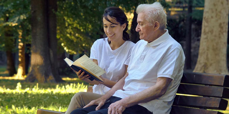 woman reading to elderly man in a park