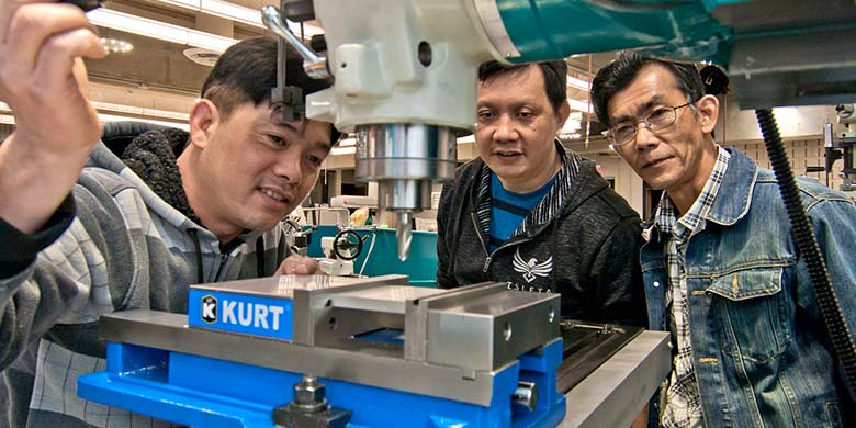 Three Men Observing a Drill Press Machine
