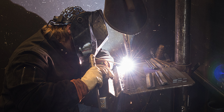 student in welding helmet working on a project