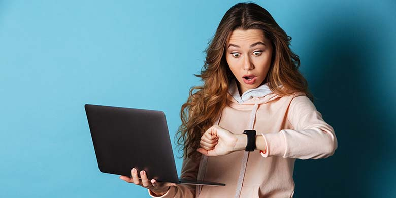 Portrait of a shocked surprised girl watching at her wristwatch while standing and holding laptop computer isolated over blue background