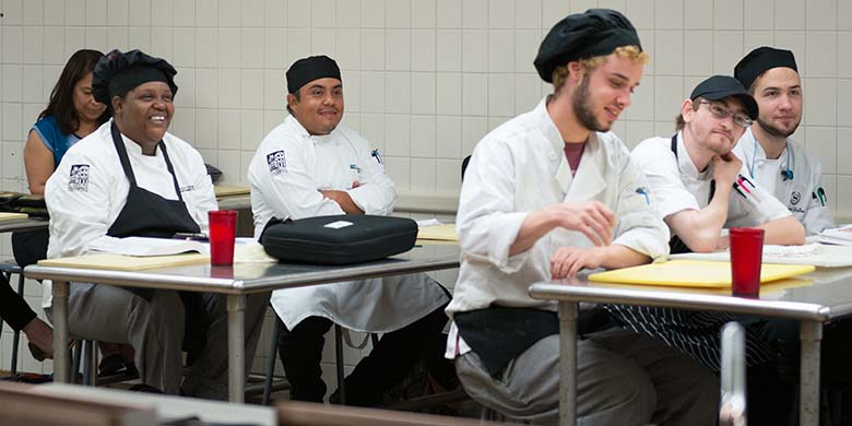 Students smiling in a culinary class in El Centro's Food and Hospitality Institute in downtown Dallas.