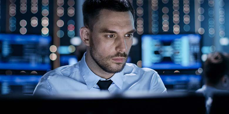 Close-up of a Professional Technical Controller Sitting at His Desk with Multiple Displays Before Him. In the Background His Colleagues Working in System Control Center.