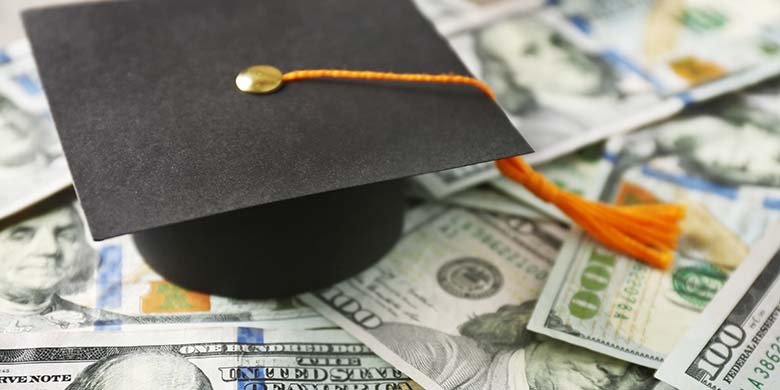 Close up view of graduation hat on dollar banknotes.