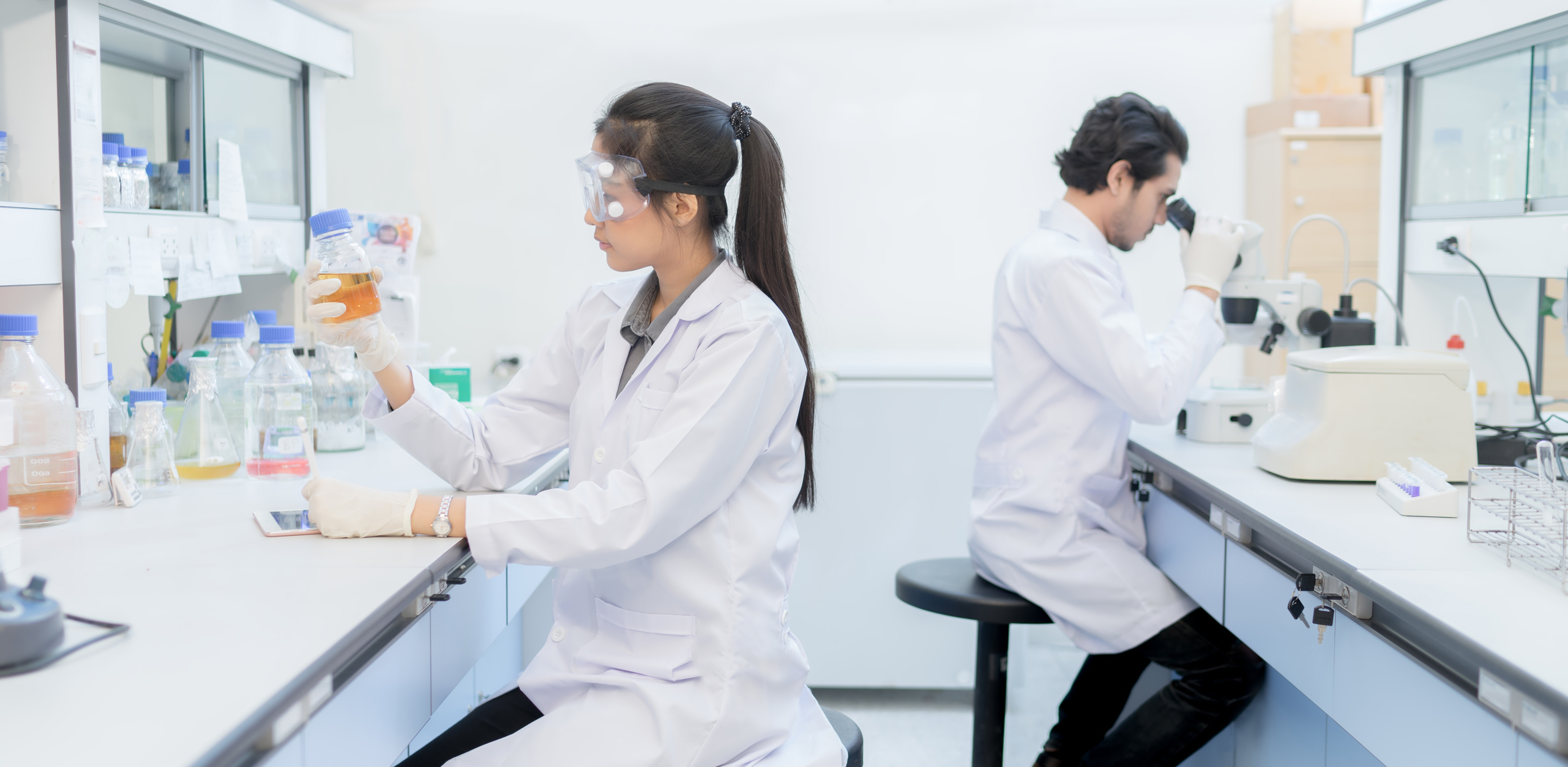 Young woman scientist in the laboratory working at lab with test tube