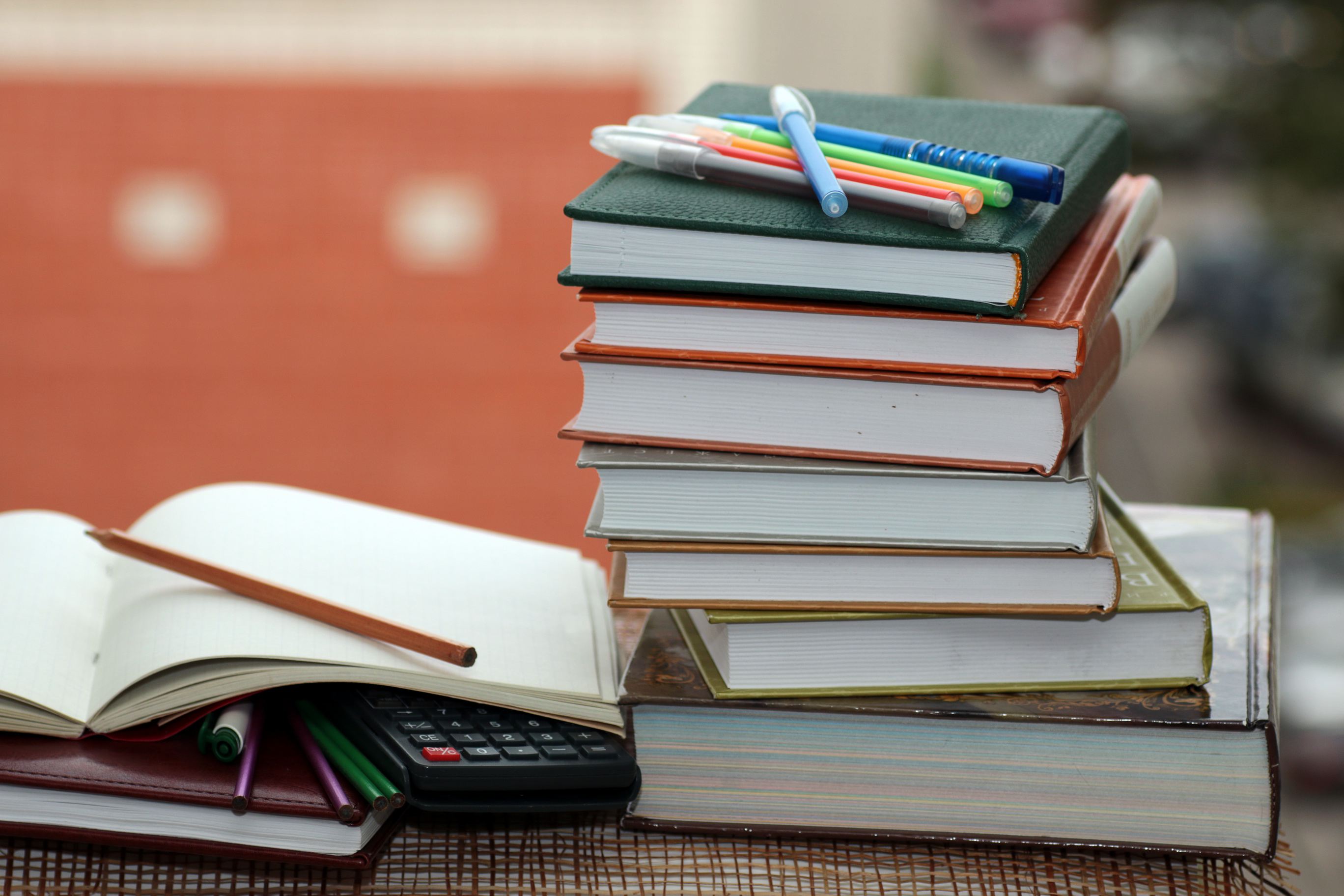 Several books stacked up with pens layed on top of stack. One book open with pencil laying across the page.