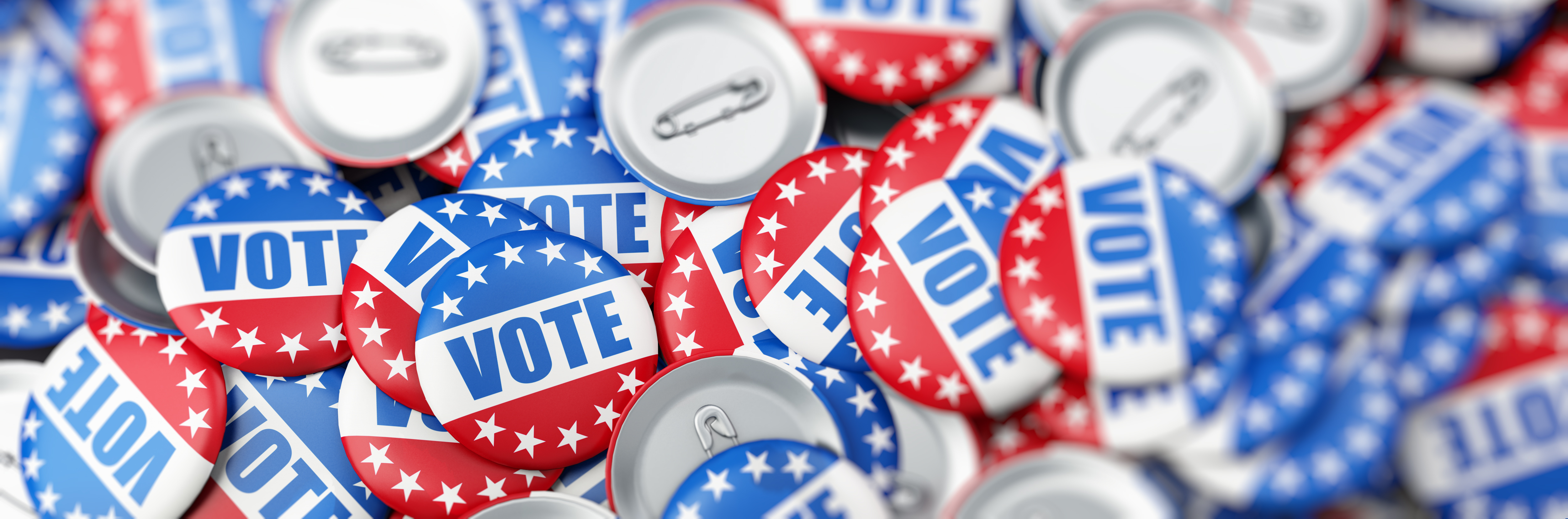 """A pile of red, white and blue buttons that say """"Vote"""""""