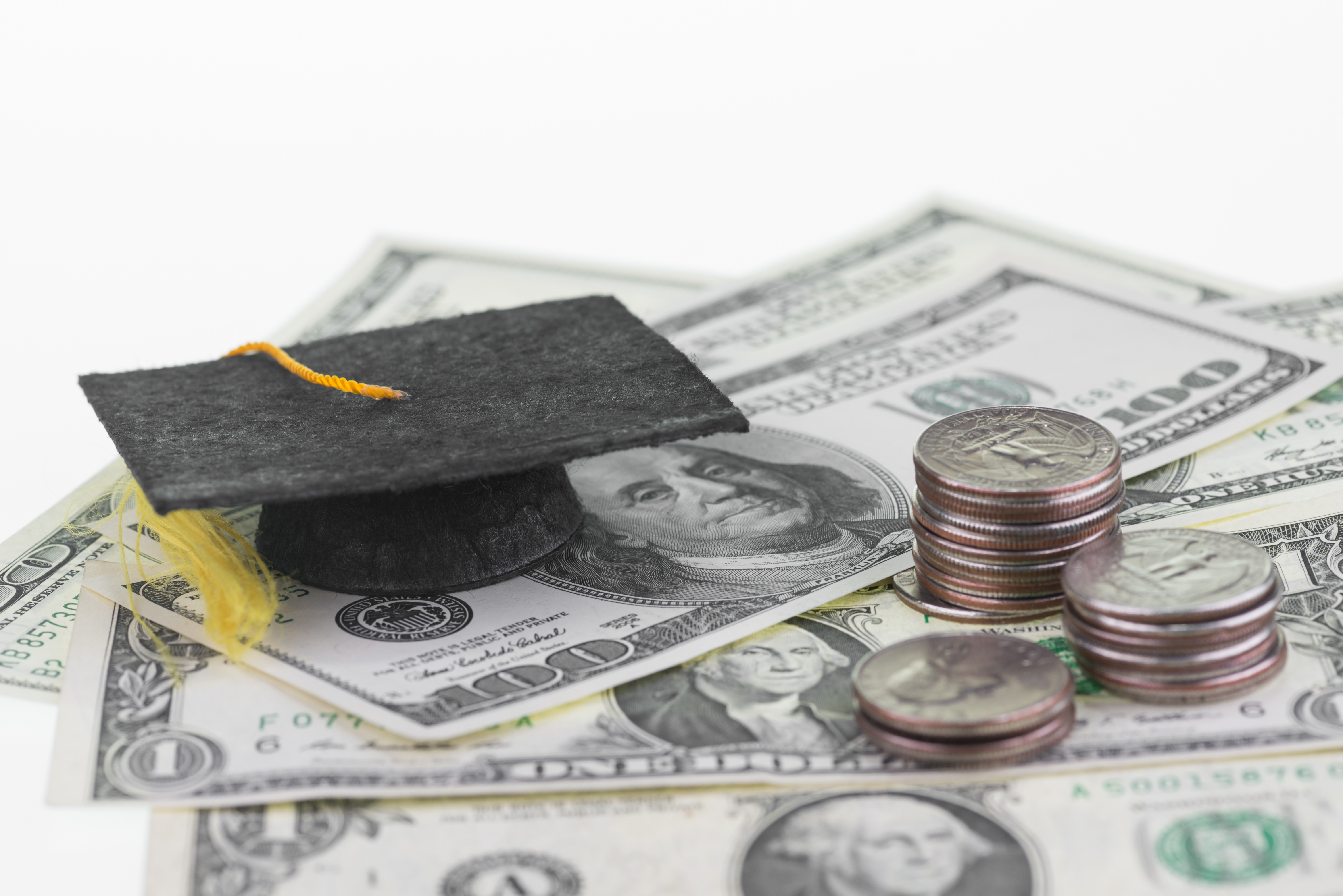 Graduation hat and coins laying on top of dollar bills.