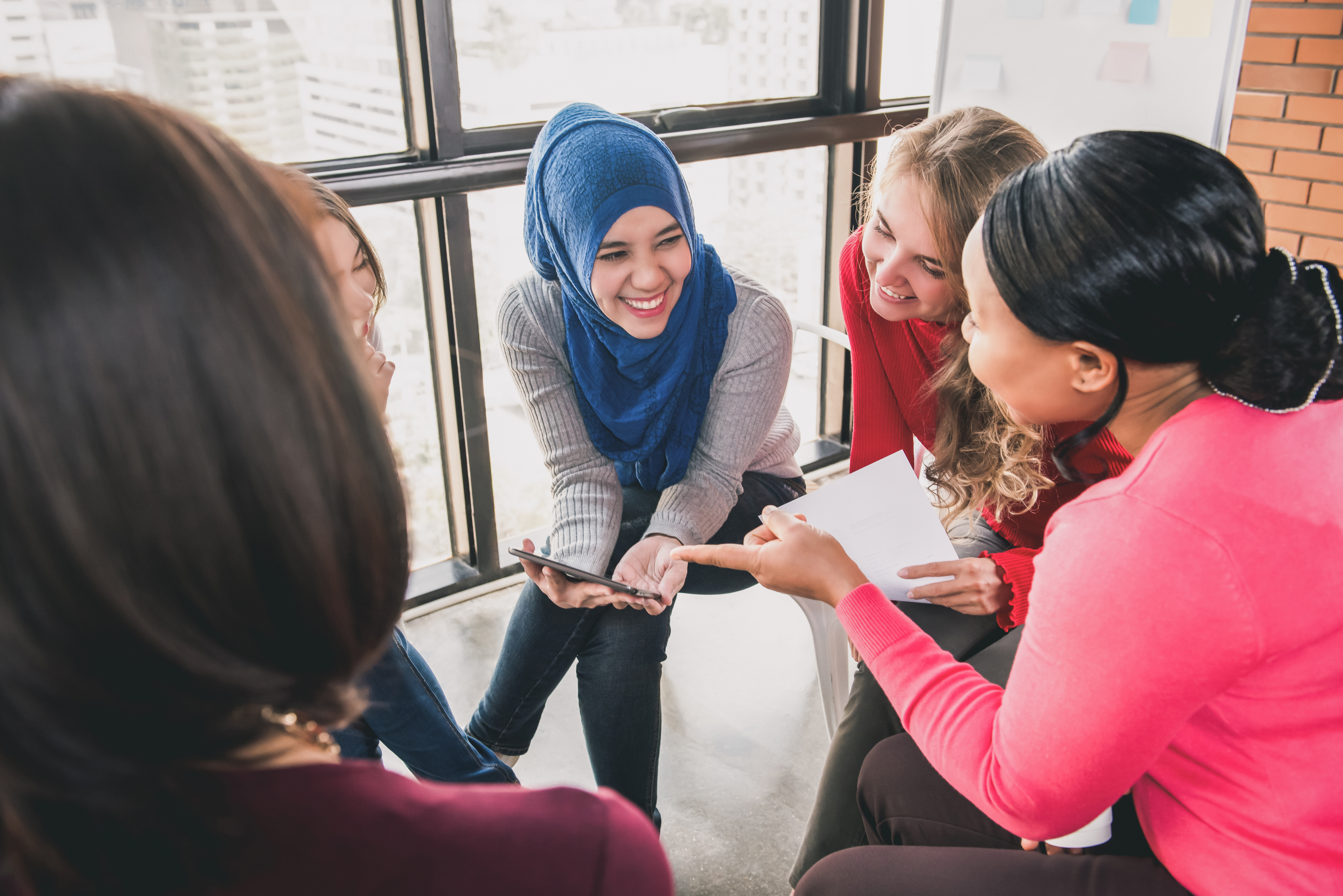 Women sitting in circle enjoying sharing stories in group meeting.