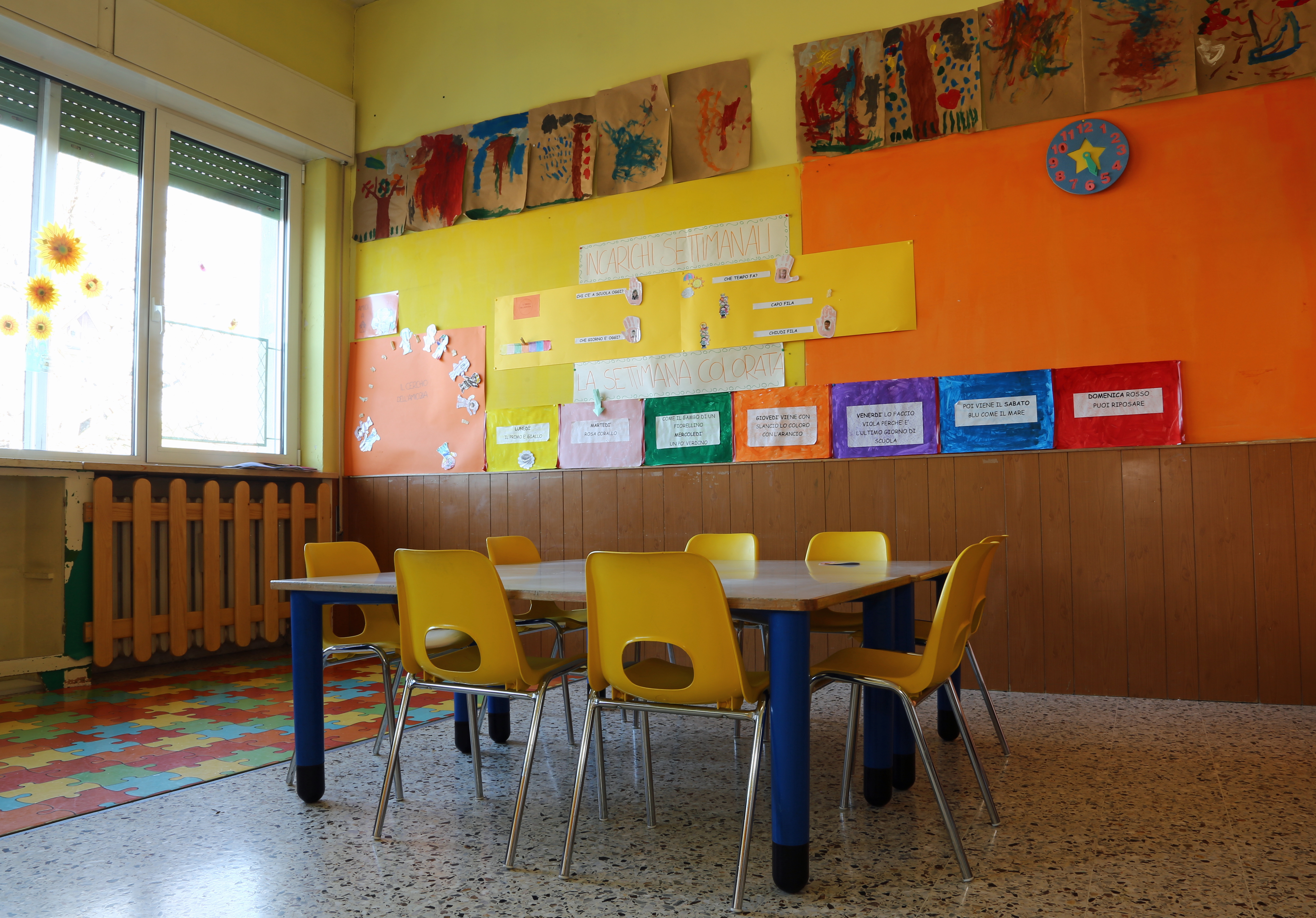 Kindergarten classroom with chairs and table with drawings.