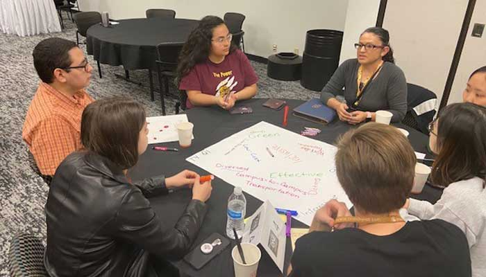 Students sitting at a table, brainstorming ideas and writing them on a poster