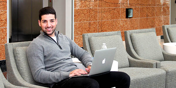 A man sits on a chair with a laptop in his lap.