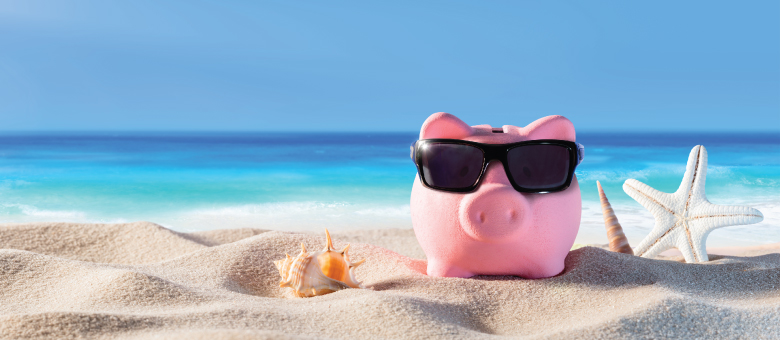 A piggy bank wearing sunglasses sits on sand in front of the ocean.