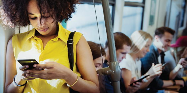 A woman looks at her phone while riding public transportation.