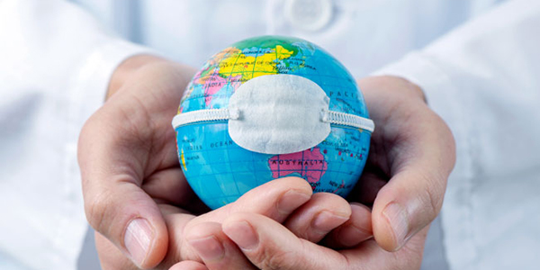 A doctor holds a globe in their hands.