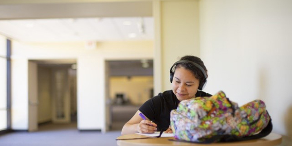 A woman studies at a desk while listening to headphones.
