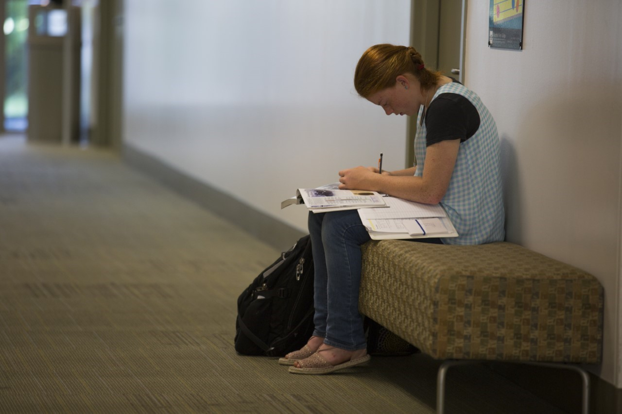 A student studies in the hallway.