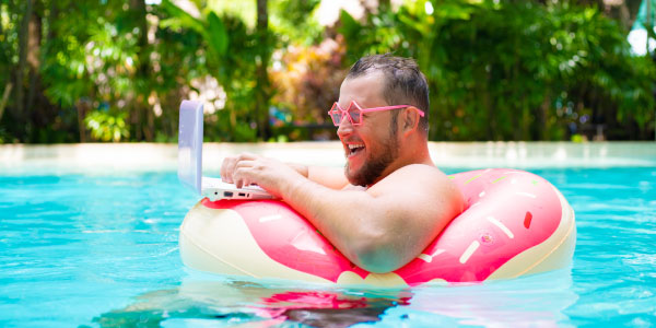 A guy wears relaxes in a float while working on a laptop in a pool.