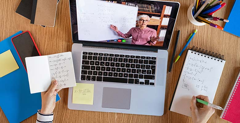 A student sits in front of a laptop listening to a lecture and taking notes.