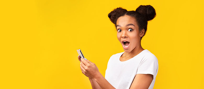 A surprised young woman looks at the camera while holding a smartphone.