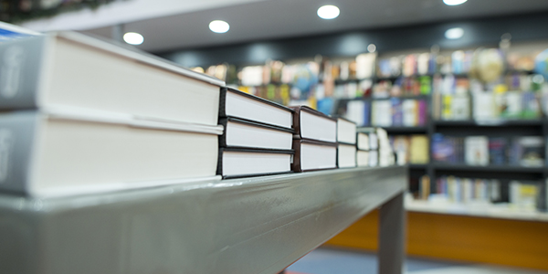 A stack of books on a table in a store.