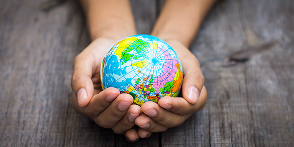 A tiny globe sits inside two hands.