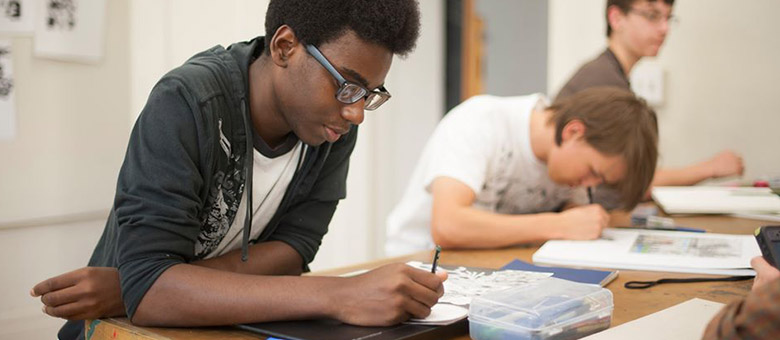 African-American student studies next to two other students.