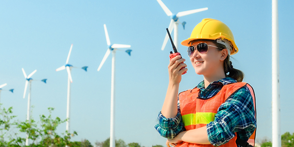 A woman wearing a hard hat speaks on handheld with windmills in the background.