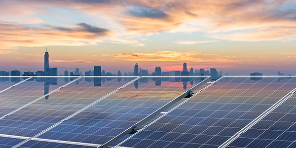Solar panels in foreground with a city in the background.