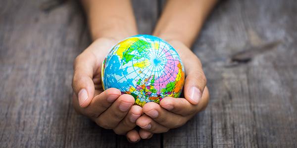 hands holding tiny globe