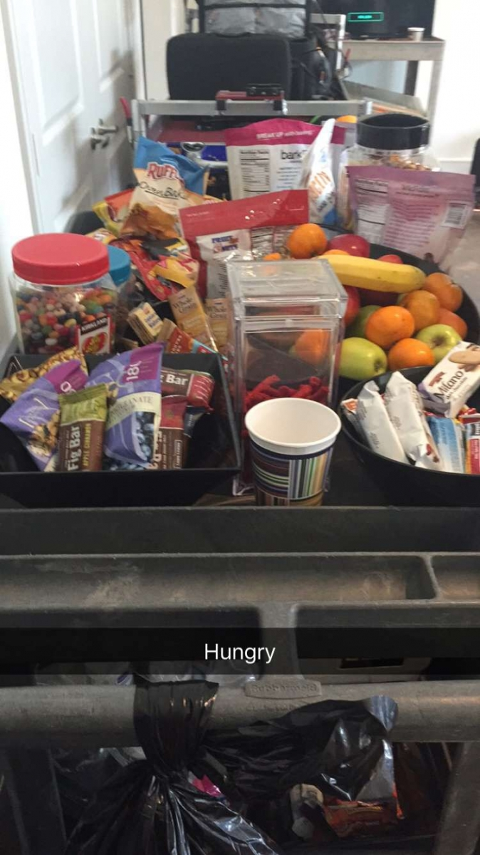 A photo of a snack cart with cookies, candy and granola bars.